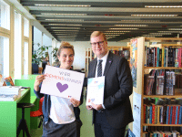 Ældre- og handicaprådmand, Søren Windell, overrækker bibliotekets demensvens-diplom til afdelingsleder på Vollsmose Bibliotek og Kulturhus, Dynke Jeppesen. Foto: Odense Kommune.